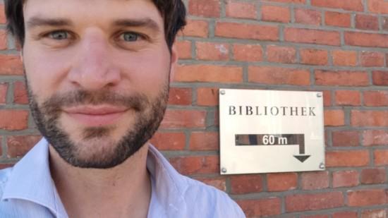 Christian Winter steht vor einer Backsteinmauer, auf der ein Schild den Weg zur Bibliothek weist.